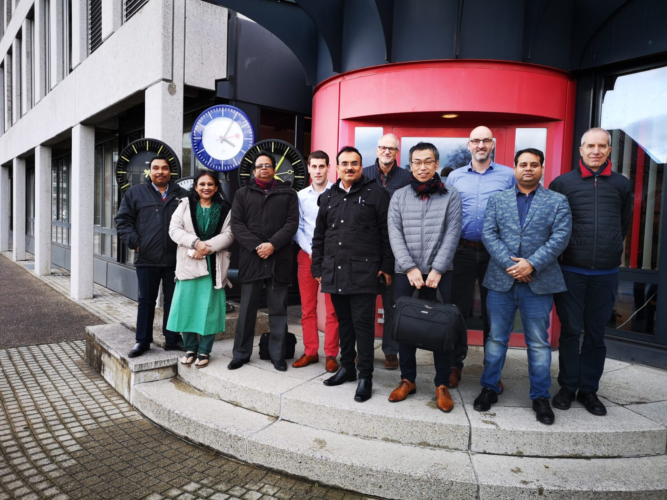 Senior Delegation representing the Dhaka Metro officials in Sumiswald with MOBATIME Team Members in front of MOBATIME Building, Analogue clocks behind left